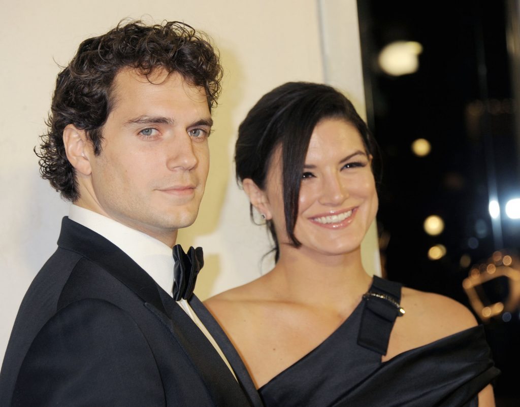 Henry Cavill and Gina Carano smiling together at a cocktail party