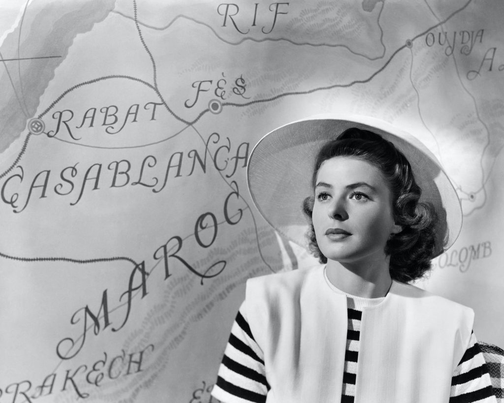 Ingrid Bergman in Casablanca, sitting in front of a map looking off camera, in black and white