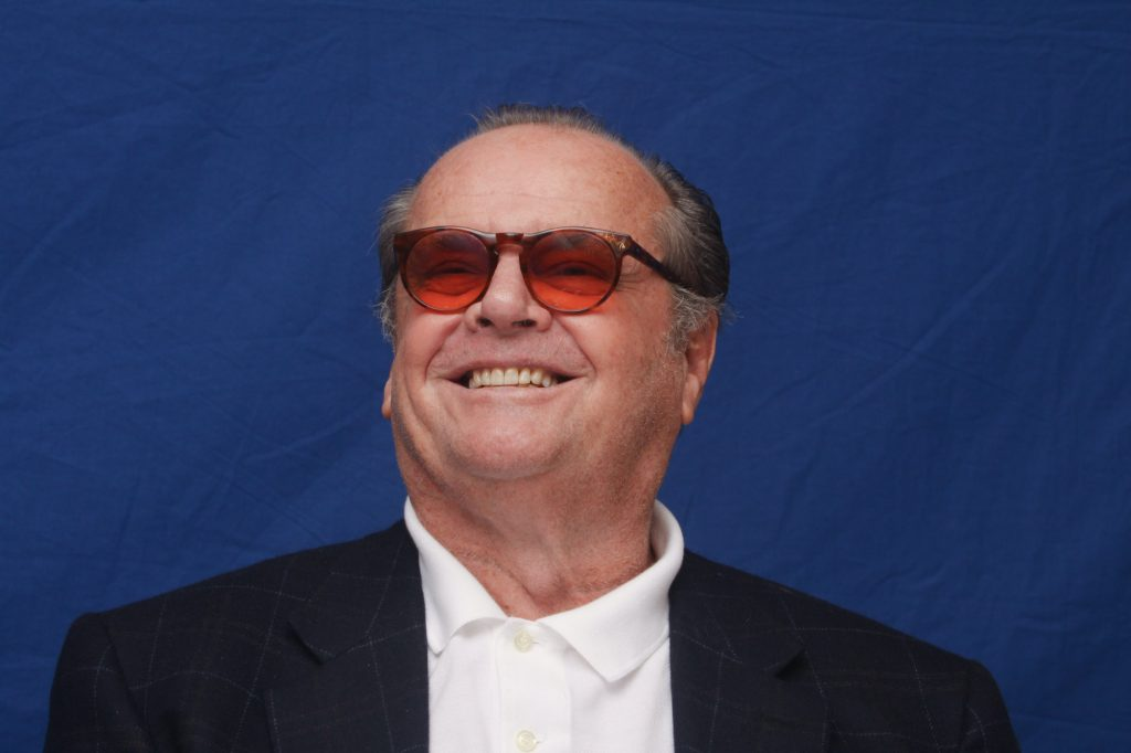 Jack Nicholson smiling in front of a blue backdrop, wearing sunglasses