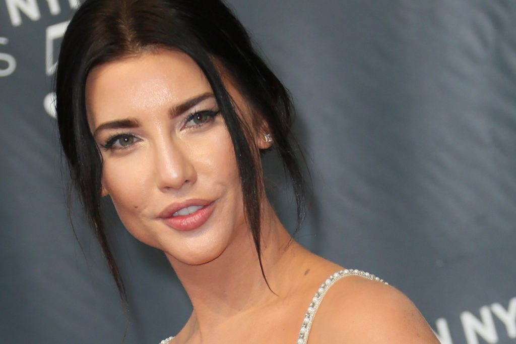 Jacqueline MacInnes Wood smiling in front of a gray background