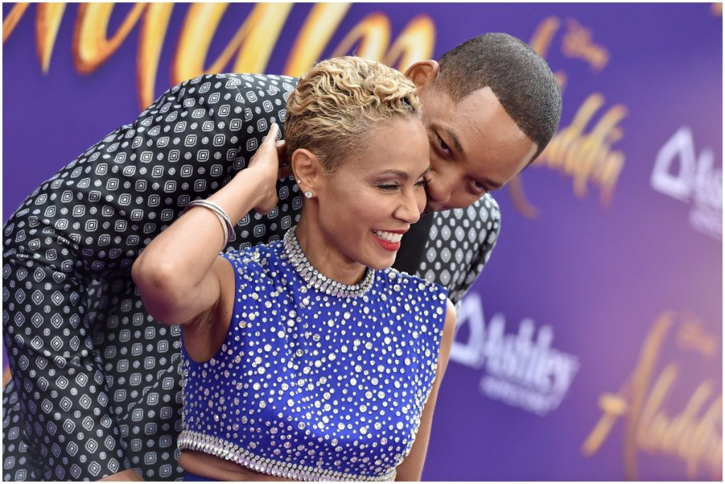 Jada Pinkett Smith and Will Smith share a kiss on the red carpet.