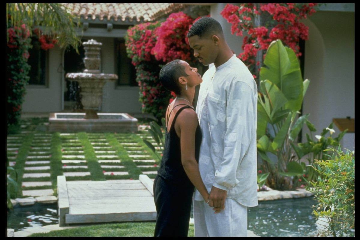 Jada Pinkett Smith smiling with a black dress on/ Will Smith wearing a white suit.