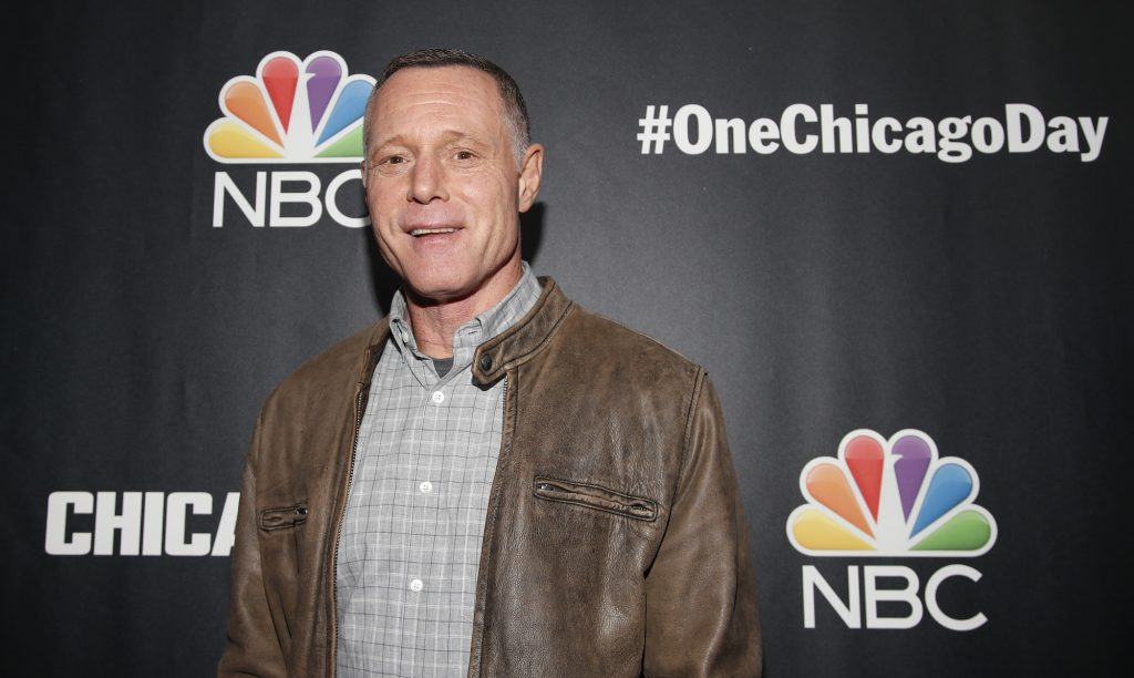 Jason Beghe smiling in front of a black backdrop
