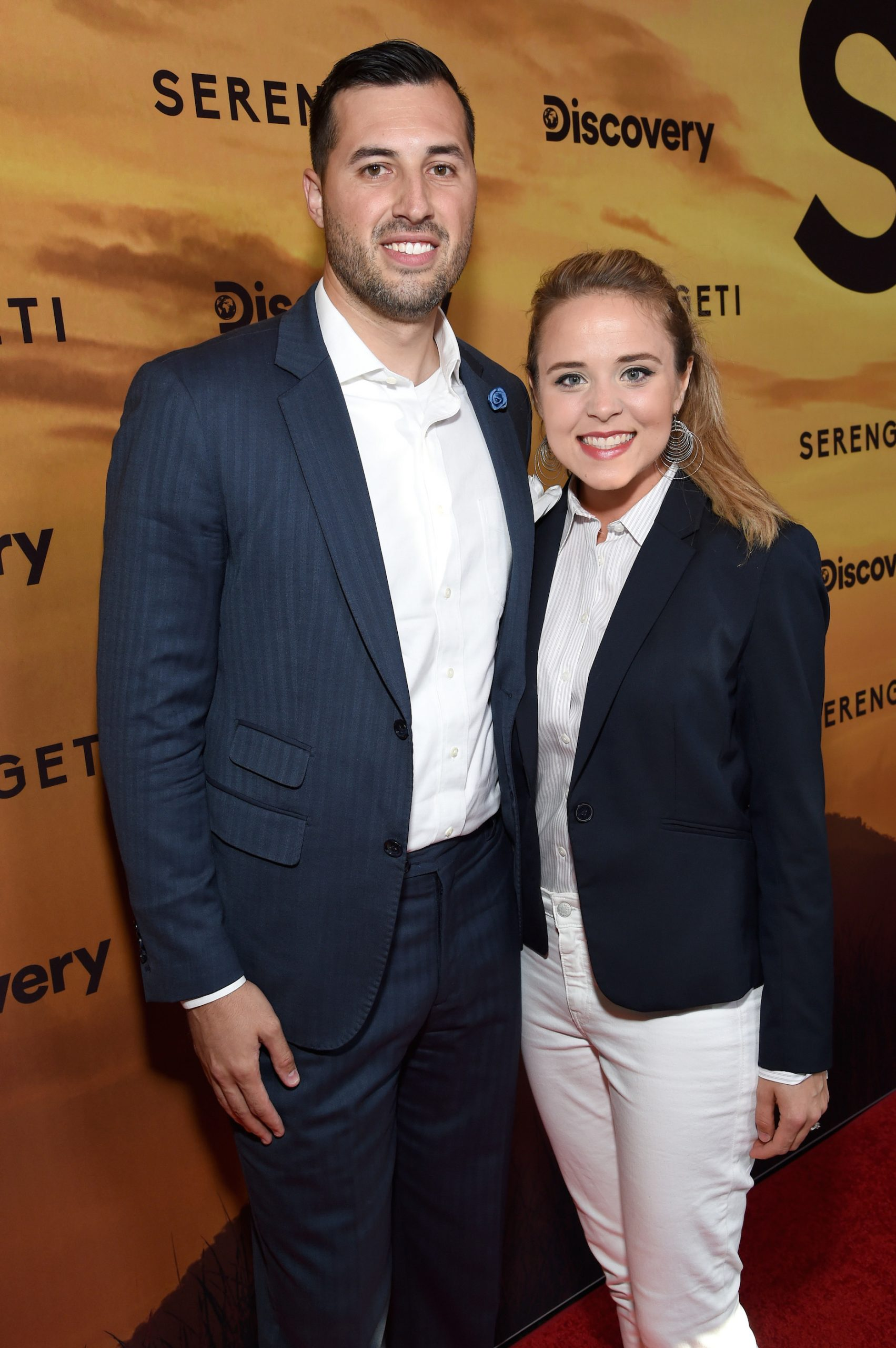 JInger Duggar, in white pants, and Jeremy Vuolo, in white shirt and blue jacket, pose at a Discovery Channel event