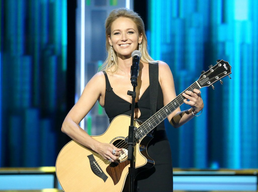 Jewel smiling on stage, holding a guitar, standing behind a microphone in front of a blue background