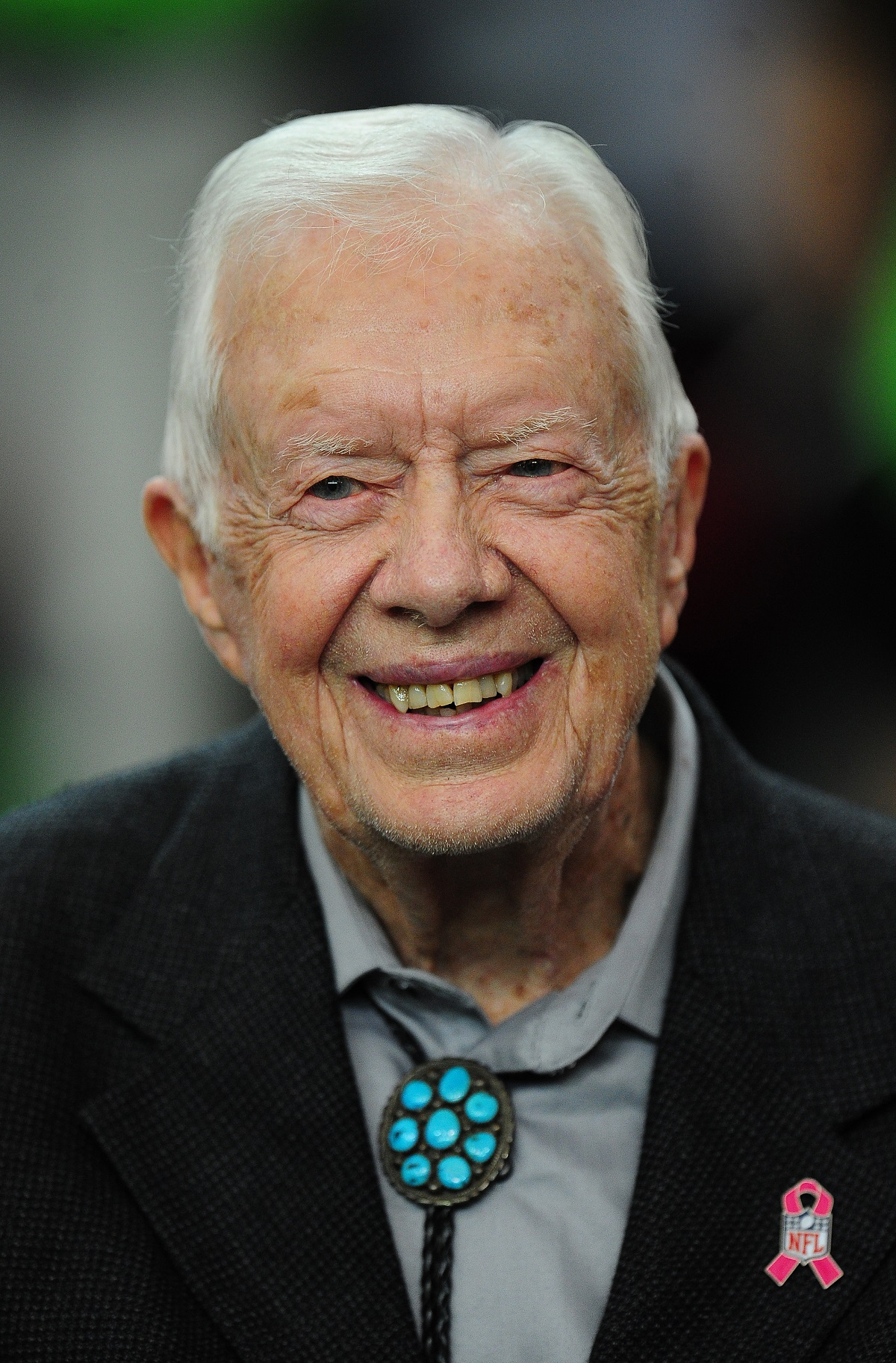 Jimmy Carter smiling at a football game in 2016