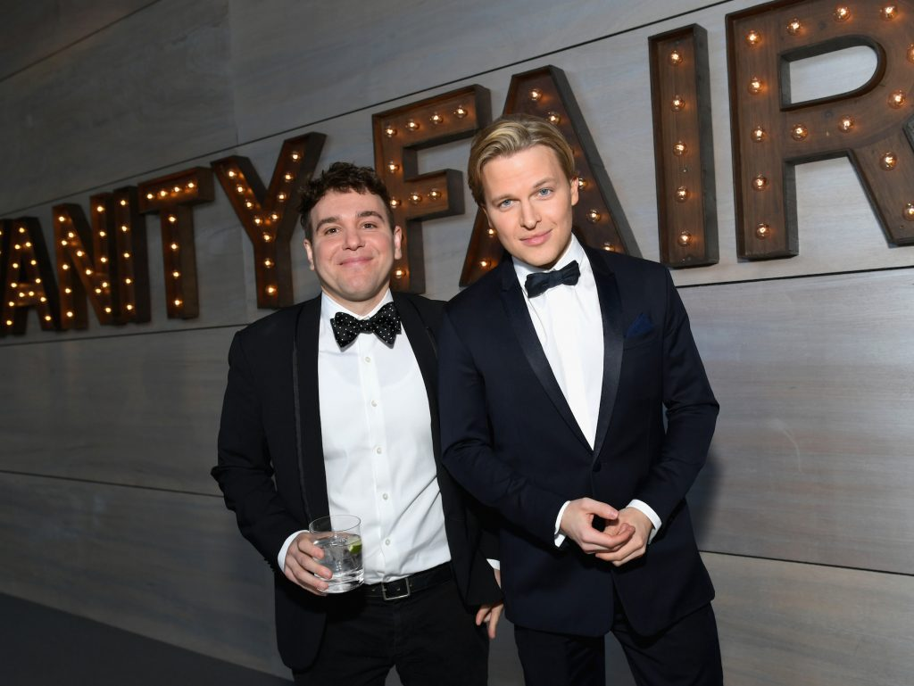 Jon Lovett and Ronan Farrow in suits standing in front of a Vanity Fair sign