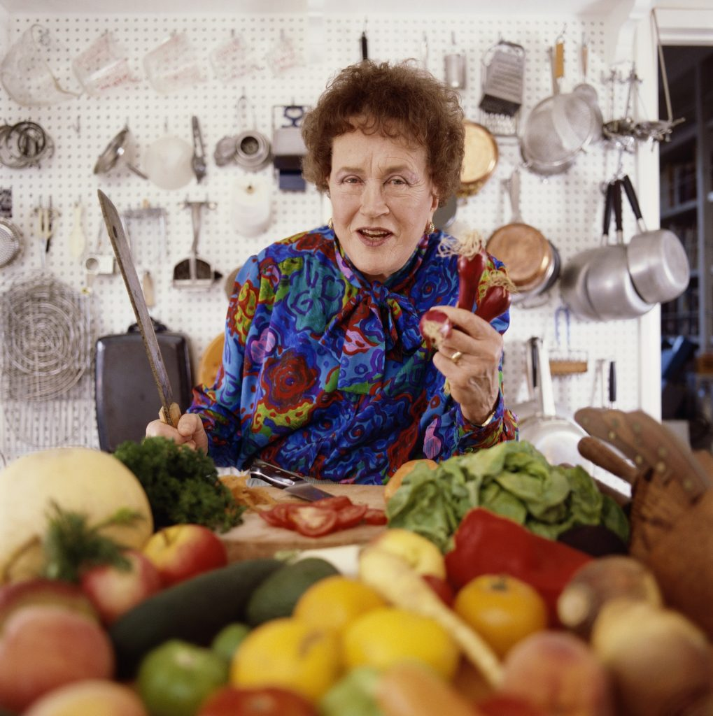 Julia Child photographed posing in her kitchen chopping vegetables