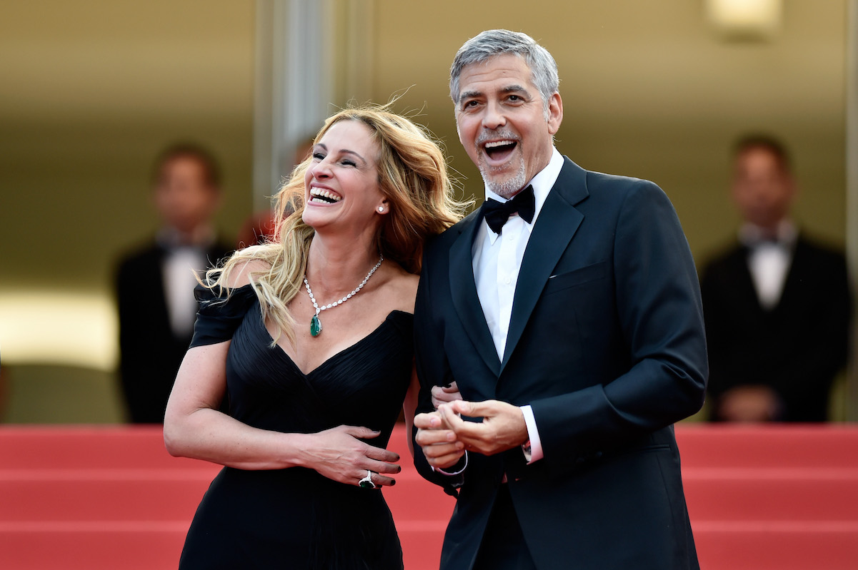 Julia Roberts and George Clooney laugh and smile on the red carpet at the 69th Annual Cannes Film Festival