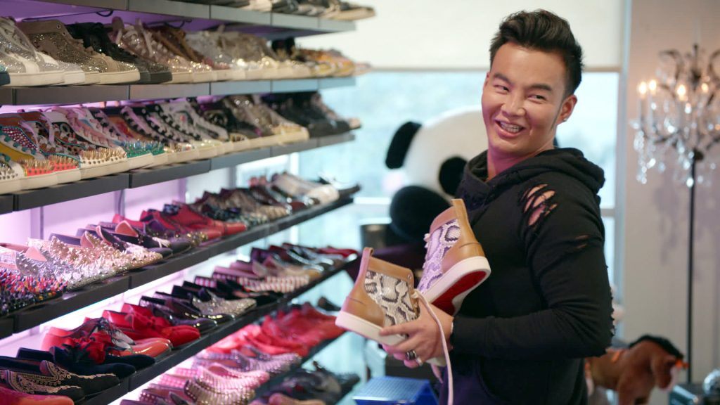Kane Lim smiling, holding a pair of shoes