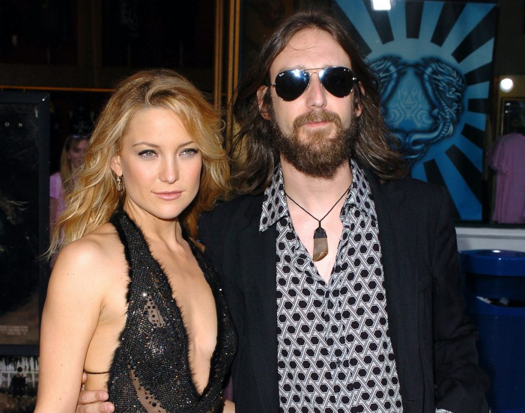 Kate Hudson in a black sleeveless dress poses with husband Chris Robinson, wearing jeans, a patterned shirt, and black blazer with sunglasses   SGranitz/WireImage