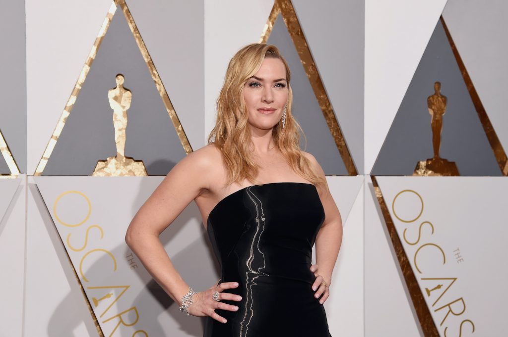 Kate Winslet smiling in front of a gray, white, and gold background