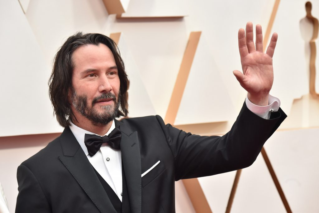 Keanu Reeves wearing a black tuxedo, waving at the 92nd Annual Academy Awards at Hollywood and Highland