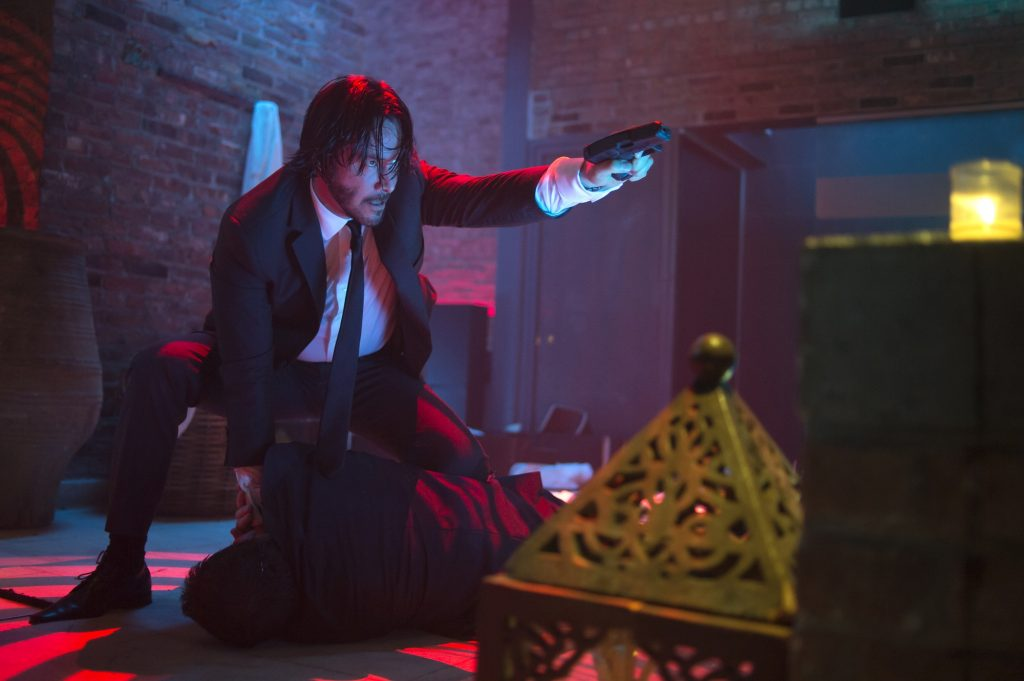 John Wick crouched and pointing a gun