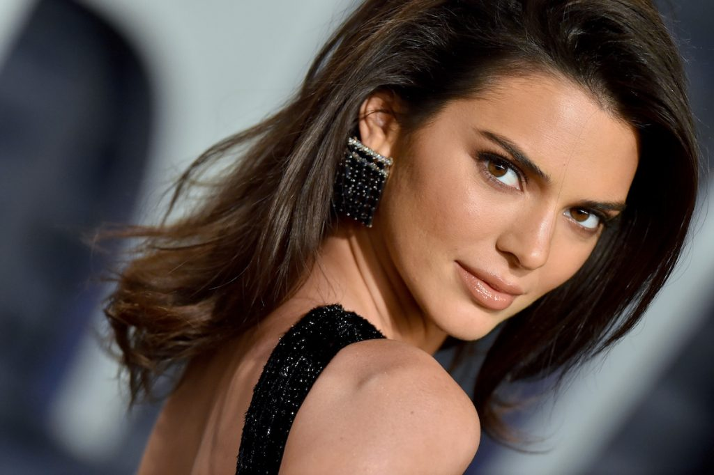 Kendall Jenner closeup with her looking over her right shoulder with hair down and neutral makeup.