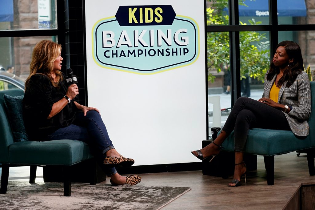 (L-R) Valerie Bertinelli and Brittany Jones-Cooper talking on a stage in front of a screen with the 'Kids Baking Championship' logo