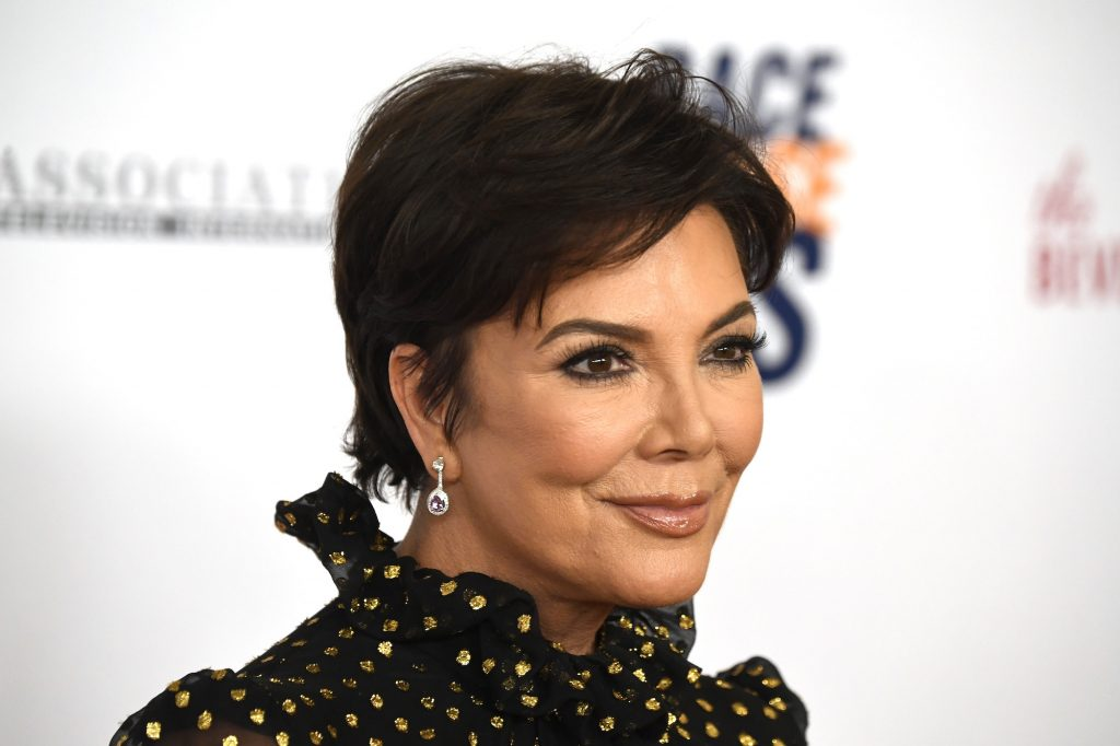 Kris Jenner smiling in front of a blurred white background, looking off camera