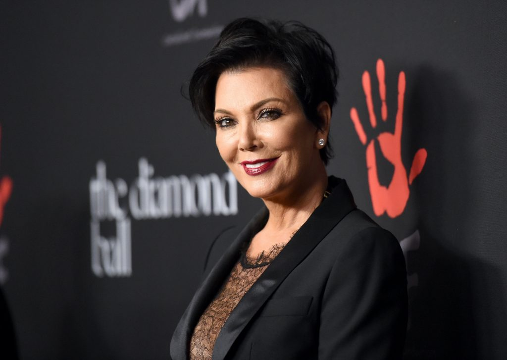 Kris Jenner smiling in front of a black background