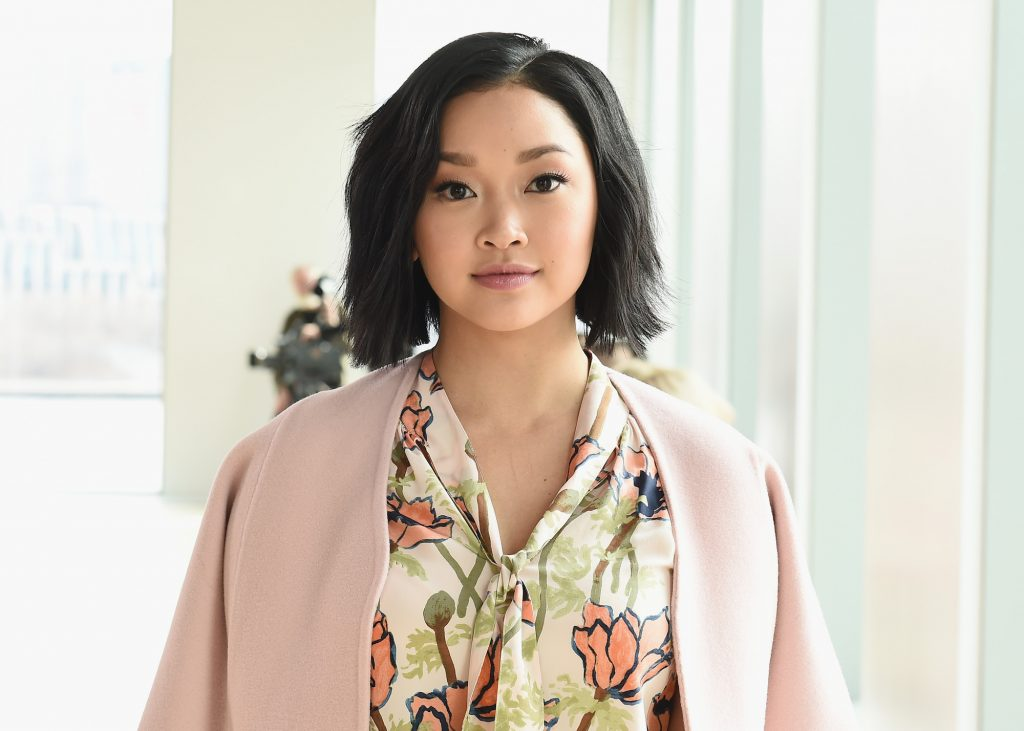 Lana Condor smiling at the camera, in front of a blurred white background