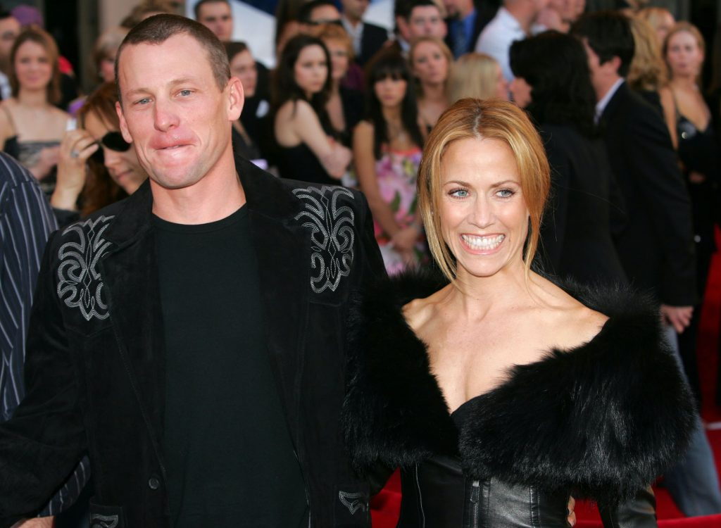 (L-R) Lance Armstrong and Sheryl Crow smiling walking on a red carpet