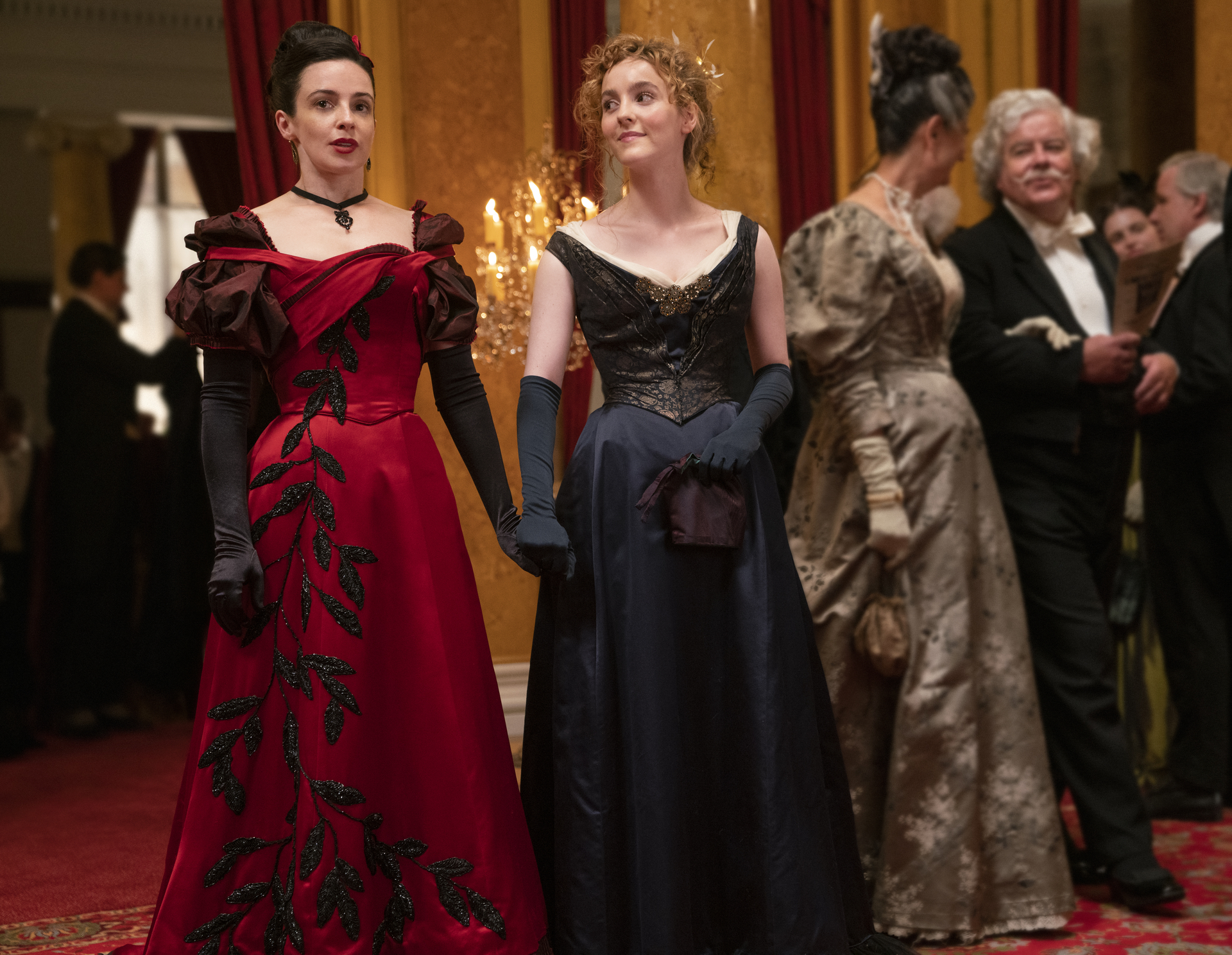 Laura Donnelly wearing a red dress holding hands with Ann Skelly wearing a black dress in The Nevers