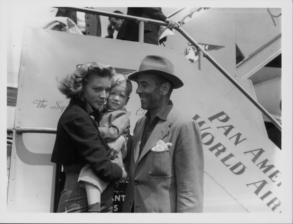 (L-R) Lauren Bacall holding a baby Stephen Humphrey Bogart, and Humphrey Bogart in front of a ship, smiling, in black and white