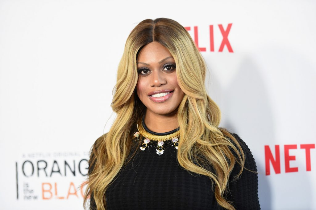 Laverne Cox staring at the camera while on the red carpet and smiling. She's wearing black and has her blonde hair down.