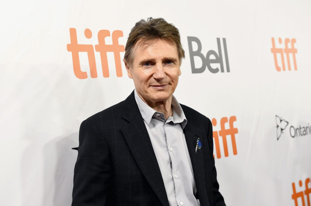 Liam Neeson smiling in front of a white background with repeating logos