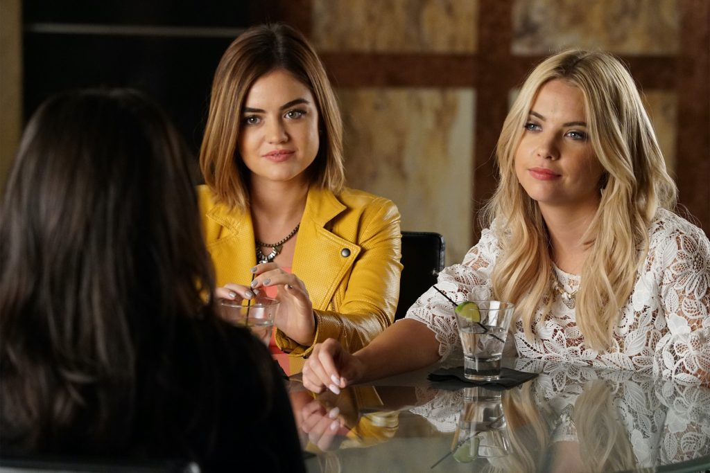 (L-R) Lucy Hale and Ashley Benson smiling, sitting at a table on 'Pretty Little Liars'