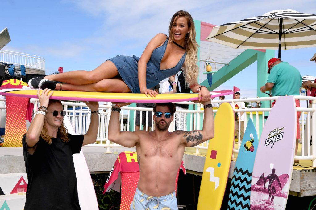 MTV 'The Challenge' star Johnny 'Bananas' Devenanzio holding Ashley Mitchell up on a surfboard on the beach