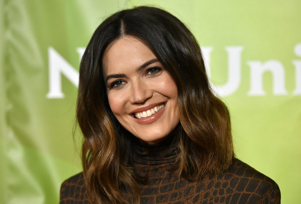 Mandy Moore smiling in a brown dress in front of a green background | Frazer Harrison/Getty Images