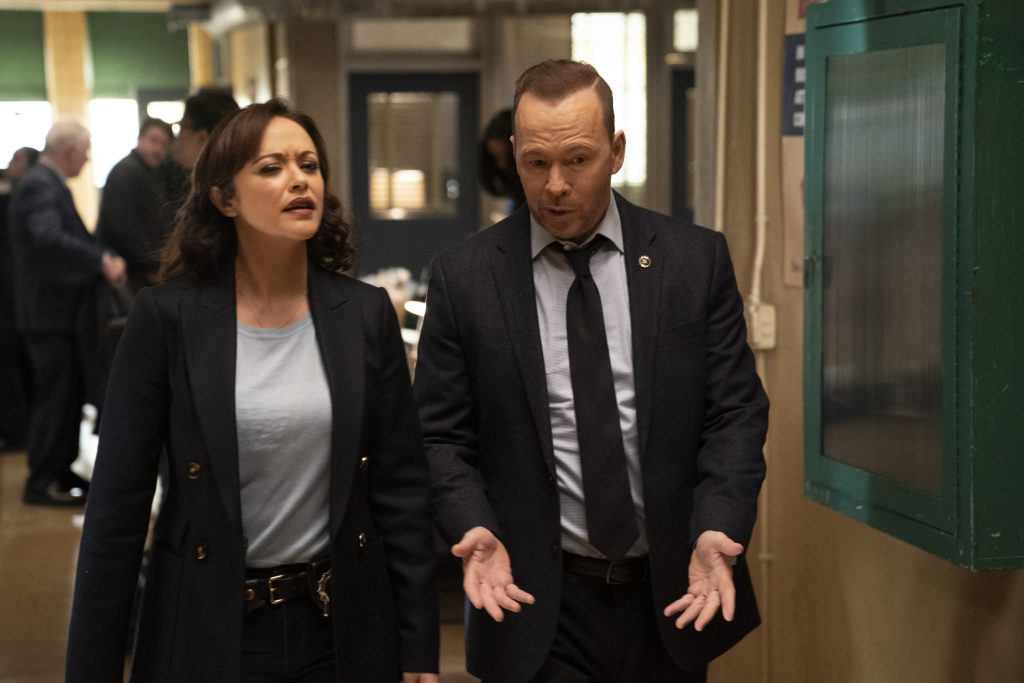 Marisa Ramirez and Donnie Wahlberg walk next to each other talking in a hallway on the set of 'Blue Bloods'