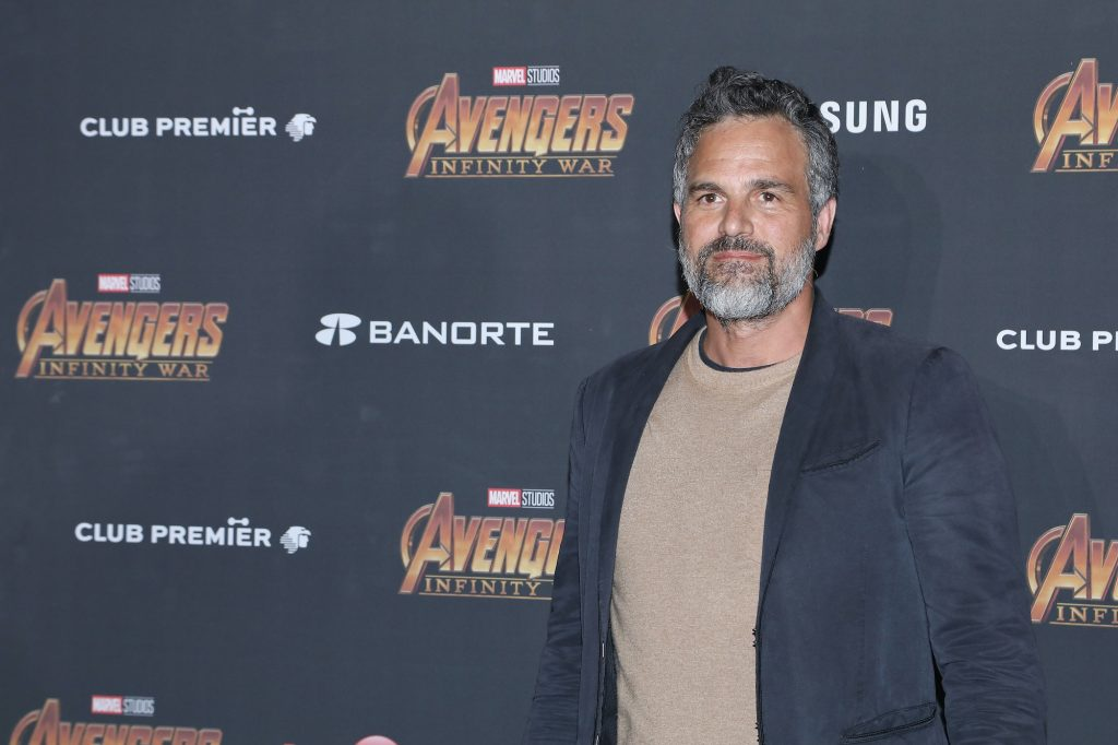Mark Ruffalo smiling in front of a gray background with repeating logos