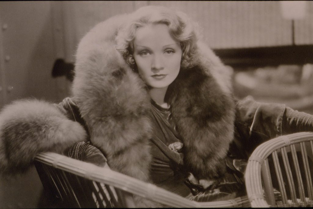 Marlene Dietrich looking at the camera with a large fur collar, in black and white