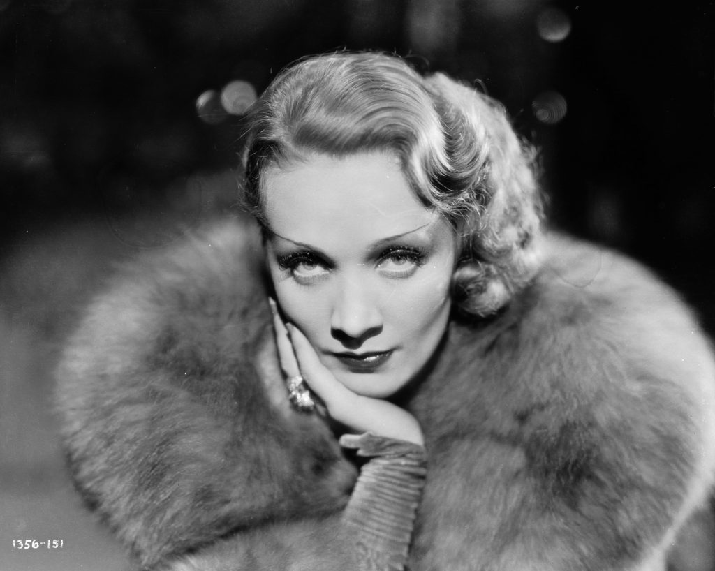 Marlene Dietrich looking up at the camera with a large fur collar, in black and white