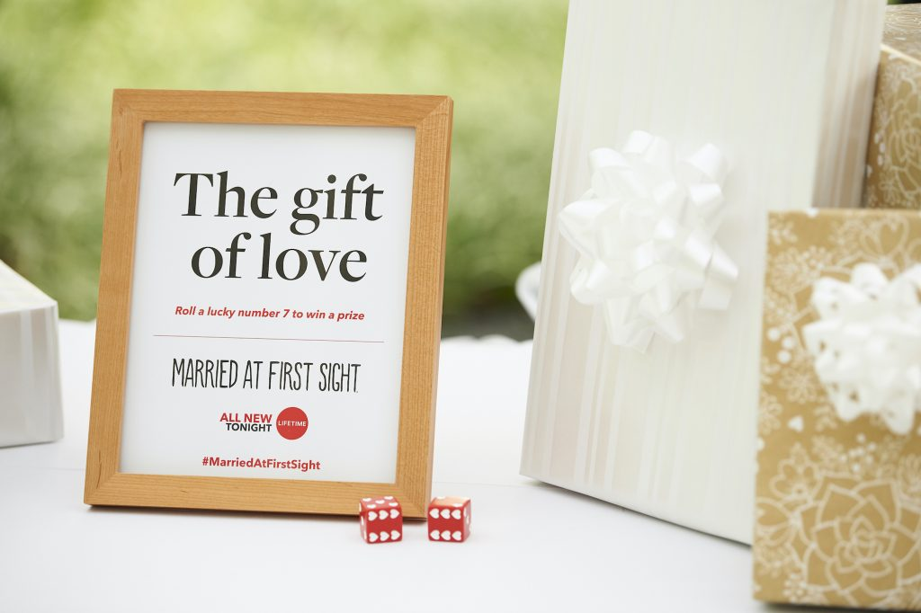 Framed sign with the Married First Sight logo on a table