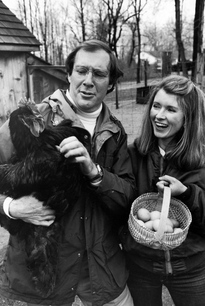 Andy Stewart holding a black Cochin hen and wife, Martha Stewart, holding a basket of eggs in barnyard