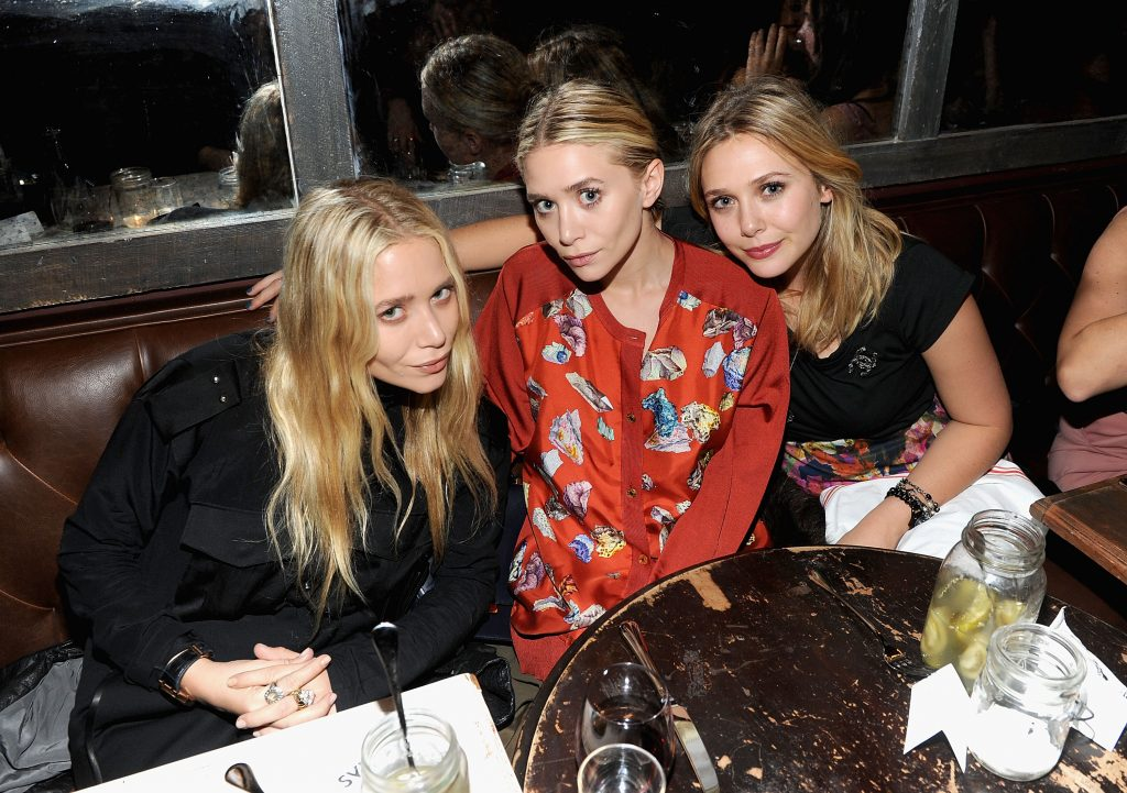 Mary-Kate Olsen in a black outfit, Ashley Olsen in a red outfit and Elizabeth Olsen in a black outfit.