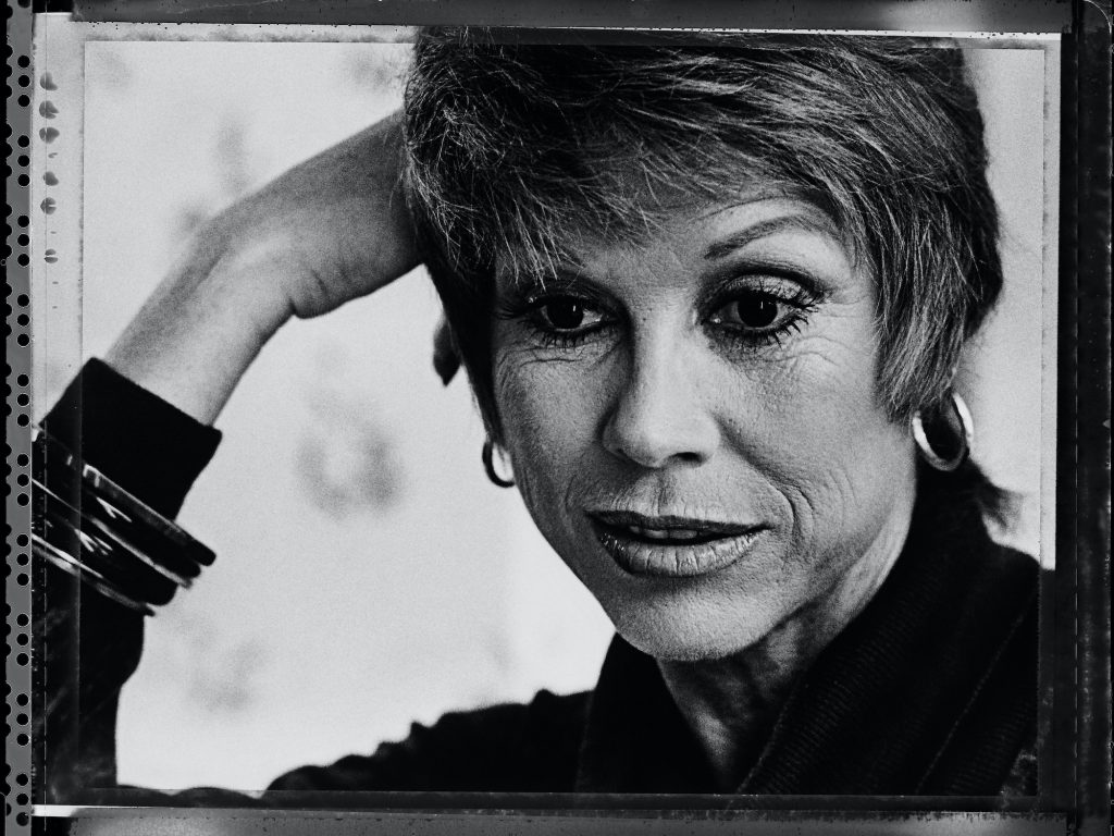 Mary Tyler Moore leaning on her hand, looking down, in black and white