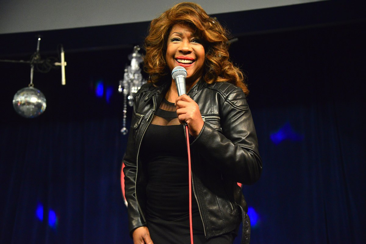 Mary Wilson stands on stage smiling and holding a microphone