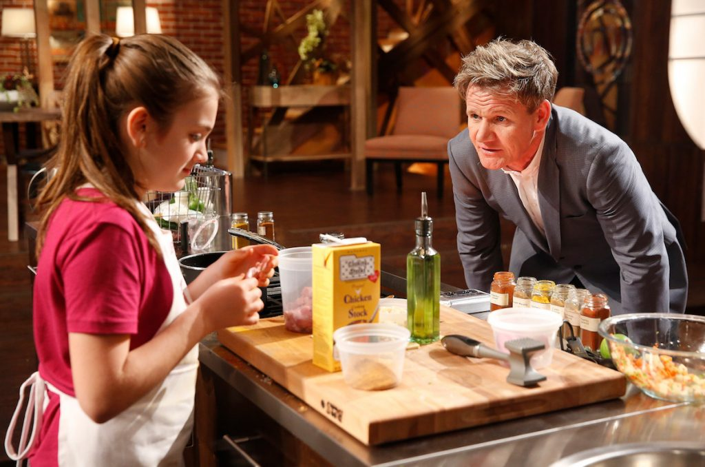 """Contestant Jenna and Gordon Ramsay in the """"Junior Edition: Grandad Gordon!"""" episode of 'MasterChef.' Ramsay is leaning over and talking to Jenna."""