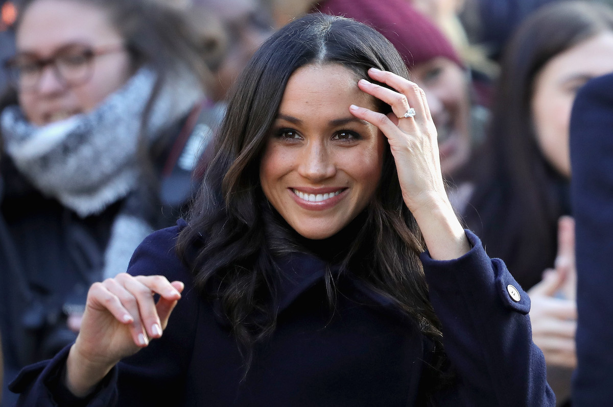 Meghan Markle smiles and brushes away a strand of hair as she arrives at the Terrance Higgins Trust World AIDS Day charity fair at Nottingham Contemporary
