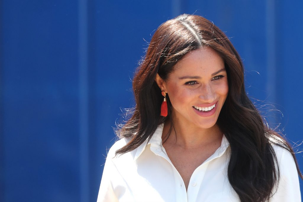 Meghan, Duchess of Sussex in South Africa smiling wearing a white shirt