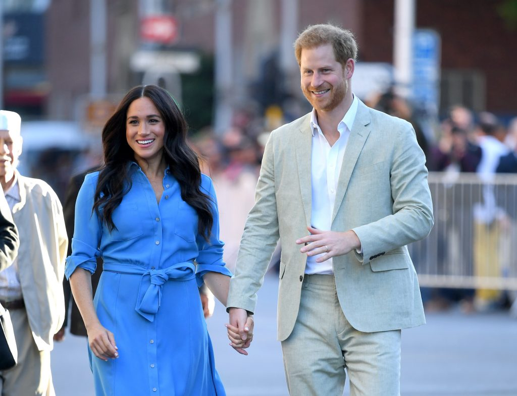 (L-R) Meghan Markle and Prince Harry smiling, walking down a street, holding hands