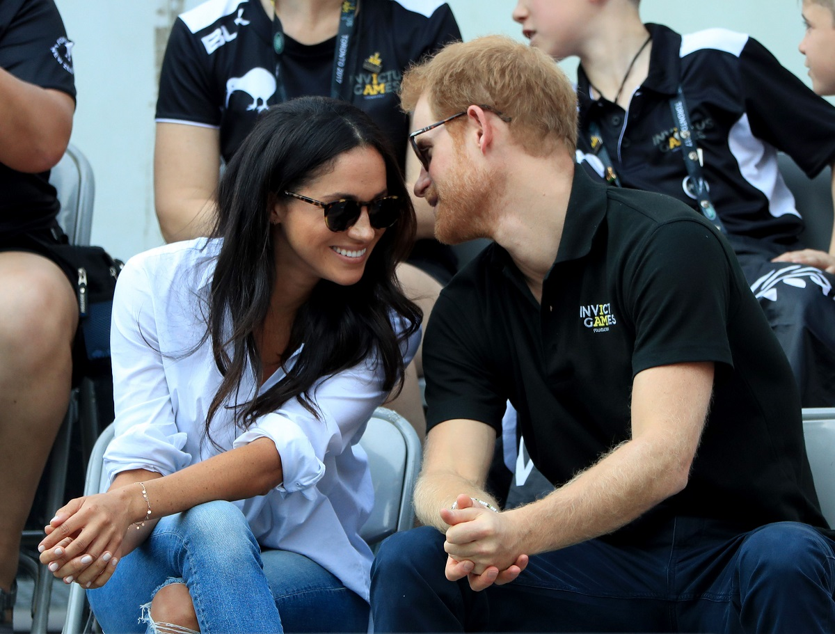 Prince Harry and Meghan Markle wearing sunglasses and leaning in to each other while watching Wheelchair Tennis in 2017