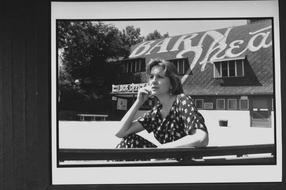 Melissa Gilbert posing on a bench in front of the Barn Theatre where she is performing in her playwright husband Bo Brinkman's new play