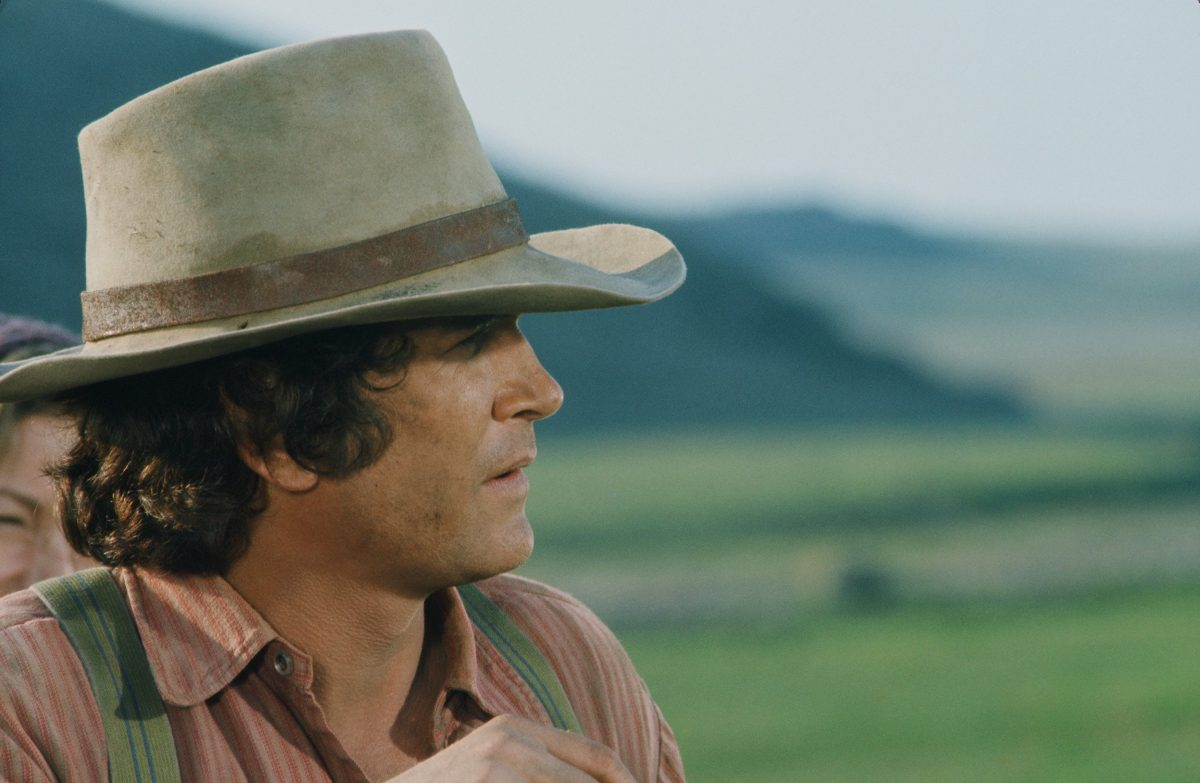 Michael Landon with a tan and brown hat and a red shirt.