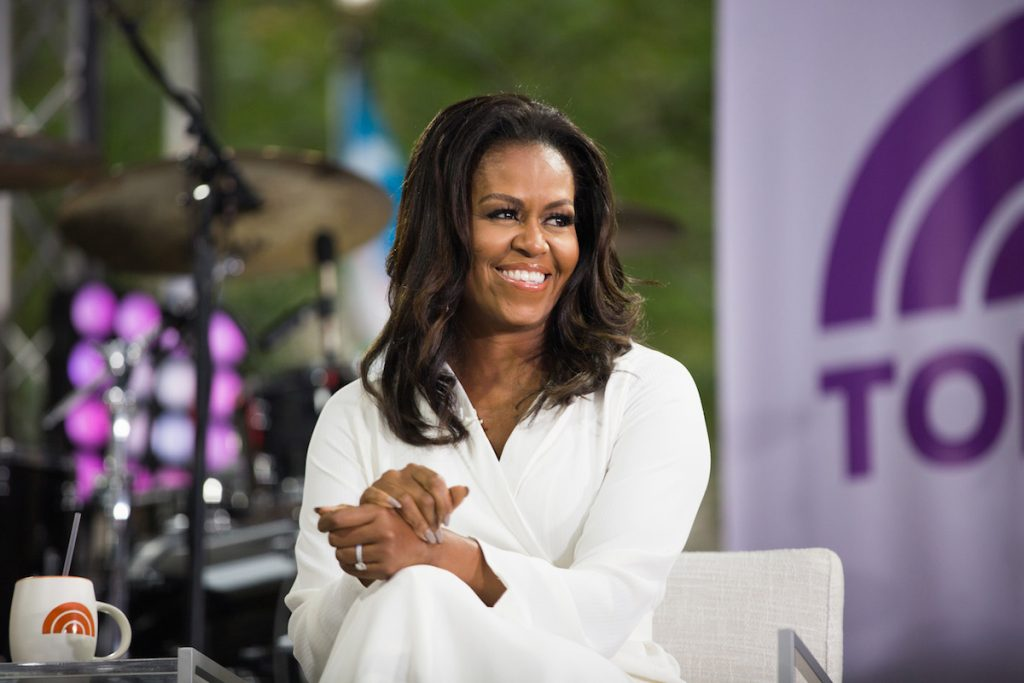Michelle Obama smiling and looking to her right wearing a white blazer.