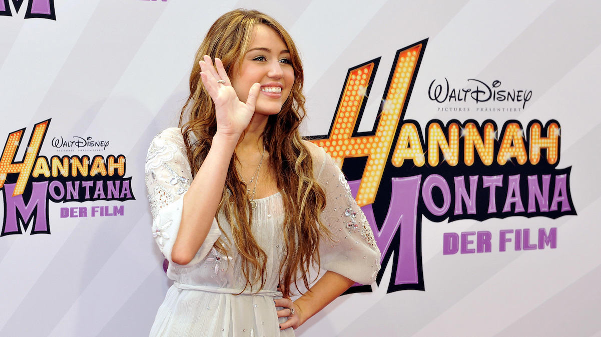 Miley Cyrus smiling and waving at the 'Hannah Montana: The Movie' German premiere.