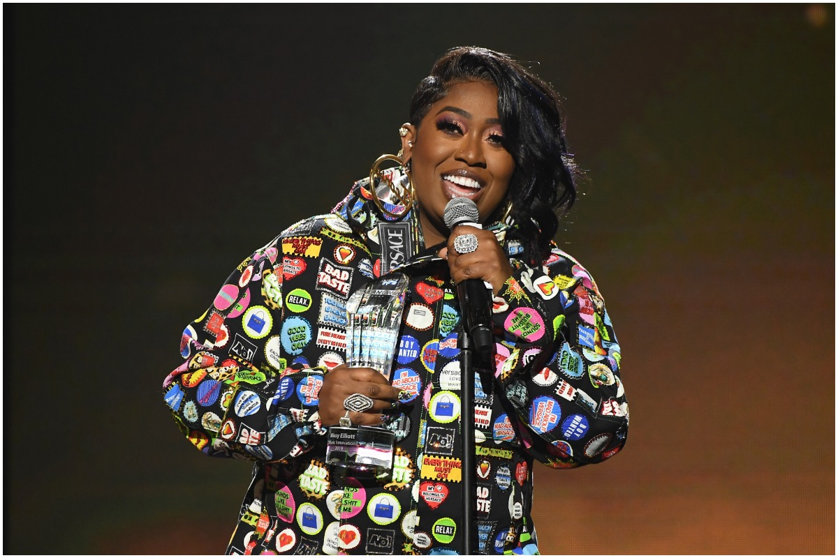 Missy Elliott smiling at an awards show wearing a rainbow jacket and gold earrings.